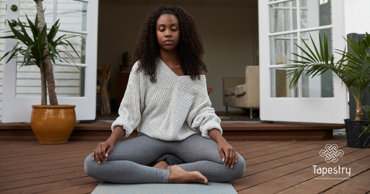 African American woman practicing yoga on her deck